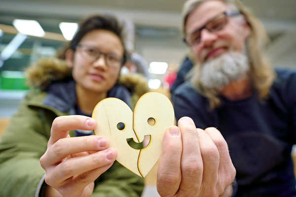 Two persons holding a heart made of wood. The heart has a smiling face.